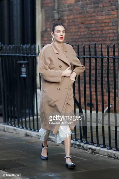 Alexa Chung wears earrings, a pale brown / beige long wool coat, a white lace mesh dress, black bejeweled shoes, during London Fashion Week Fall...