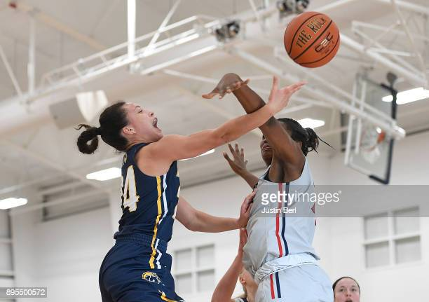 Alexa Golden of the Kent State Golden Flashes is fouled by Mikalah Mulrain of the Robert Morris Colonials as she goes to the basket for a lay up in...