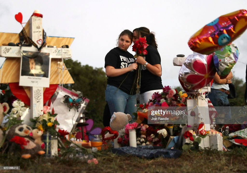 Alexa Mesch (L) and Heather Mesch place flowers in a makeshift memorial setup in front of Marjory Stoneman Douglas High School in memory of the 17 people that were killed on February 14, on February 21, 2018 in Parkland, Florida. Police arrested 19-year-old former student Nikolas Cruz for killing 17 people at the high school.