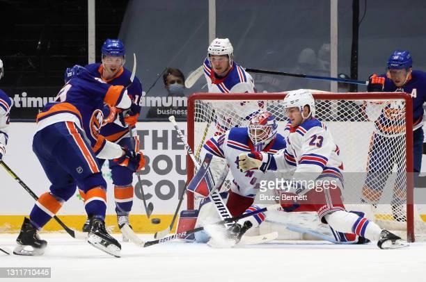 Alexandar Georgiev and Adam Fox of the New York Rangers block the net against Brock Nelson of the New York Islanders at Nassau Coliseum on April 09,...