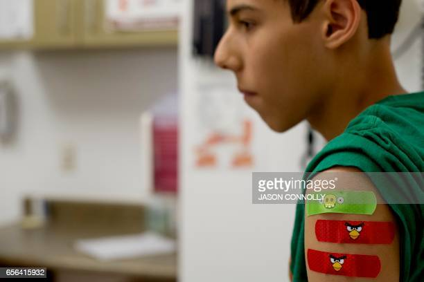 Alexander Alaron waits to be discharged from Inner City Health Center in Denver Colorado after receiving five school required vaccines on March 15...