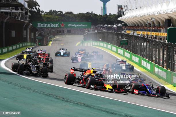 Alexander Albon of Thailand driving the Aston Martin Red Bull Racing RB15 and Pierre Gasly of France driving the Scuderia Toro Rosso STR14 Honda...