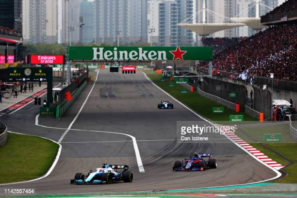 Alexander Albon of Thailand driving the Scuderia Toro Rosso STR14 Honda follows George Russell of Great Britain driving the Rokit Williams Racing...