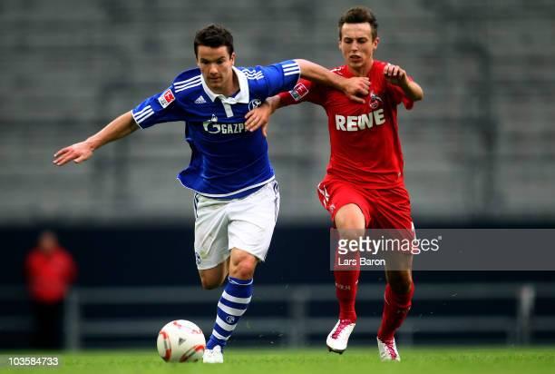 Alexander Baumjohann of Schalke is challenged by Adam Matuschyk of Koeln during a friendly match between FC Schalke 04 and 1 FC Koeln at Veltins...