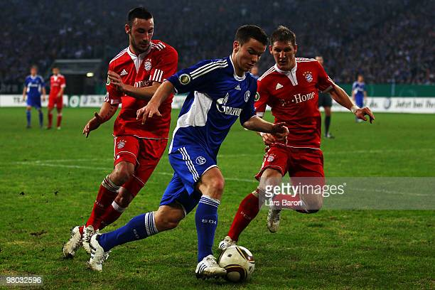 Alexander Baumjohann of Schalke is challenged by Diego Contento and Bastian Schweinsteiger of Muenchen during the DFB Cup semi final match between FC...