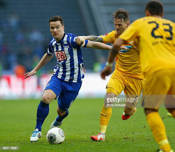 Alexander Baumjohanni of Berlin is challenged by Sejad Salihovic and Eugen Polanski of Hoffenheim during the Bundesliga match between Hertha BSC and...