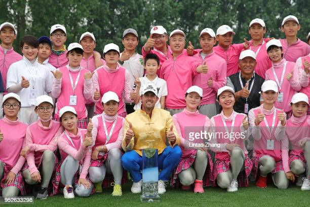 Alexander Bjork of Sweden holds the trophy with volunteers celebrates after winning the 2018 Volvo China Open at Topwin Golf and Country Club on...