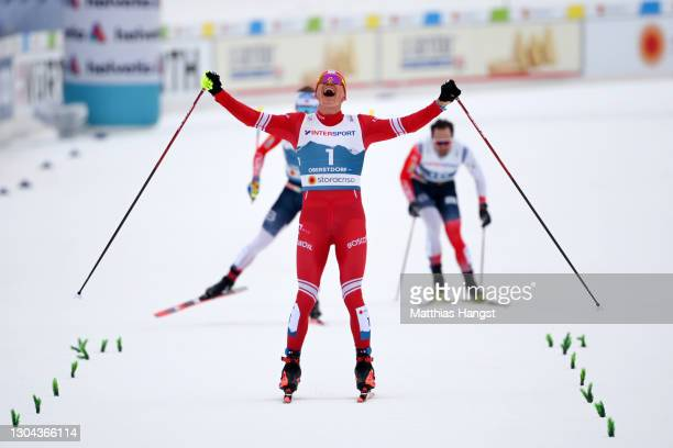 Alexander Bolshunov of Russian Ski Federation celebrates on the home stretch as he approaches the finish line to win the Men's Cross Country...