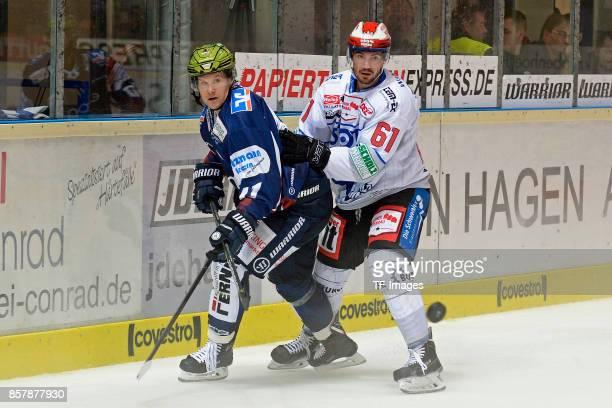 Alexander Bonsaksen of Iserlohn and Mirko Hoefflin of Schwenningen battle for the ball during the DEL match between Iserlohn Roosters and...