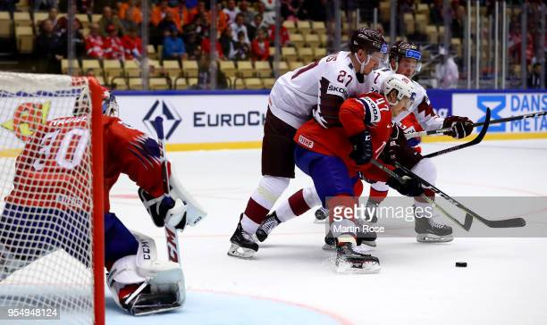 Alexander Bonsaksen of Norway and Oskars Cibulskis of Latvia battle for the puck during the 2018 IIHF Ice Hockey World Championship group stage game...