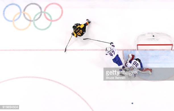 Alexander Bonsaksen of Norway collides with goalie Lars Haugen against Yasin Ehliz of Germany in the first period during the Men's Ice Hockey...