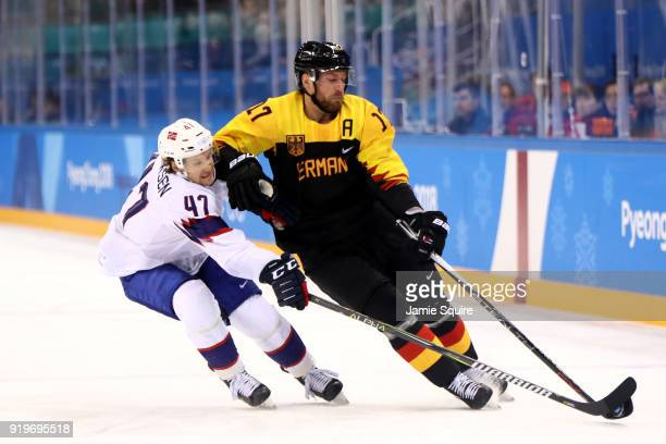 Alexander Bonsaksen of Norway competes for the puck with Marcus Kink of Germany in the first period during the Men's Ice Hockey Preliminary Round...