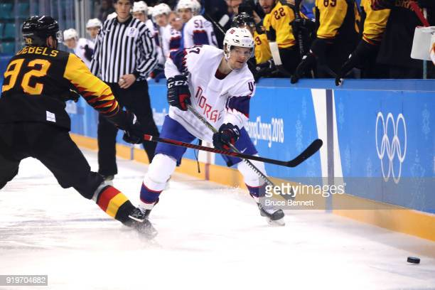 Alexander Bonsaksen of Norway fires the puck against Marcel Noebels of Germany in the third period during the Men's Ice Hockey Preliminary Round...