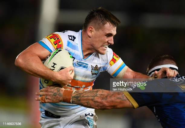 Alexander Brimson of the Titans is tackled by Josh McGuire of the Cowboys during the round eight NRL match between the North Queensland Cowboys and...