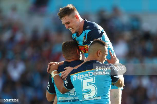 Alexander Brimson of the Titans jumps as team mate Brenko Lee celebrates a try during the round 20 NRL match between the Gold Coast Titans and the...