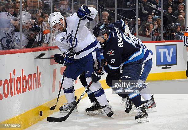 Alexander Burmistrov of the Winnipeg Jets battles Teddy Purcell of the Tampa Bay Lightning for the loose puck along the boards during third period...