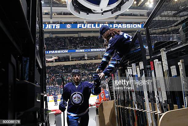 Alexander Burmistrov of the Winnipeg Jets fist bumps fans as he leaves the ice following the pregame warm up prior to NHL action against the...