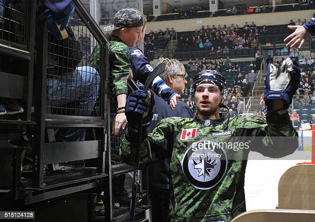 Alexander Burmistrov of the Winnipeg Jets high fives fans as he leaves the ice following the pregame warm up prior to NHL action against the Edmonton...