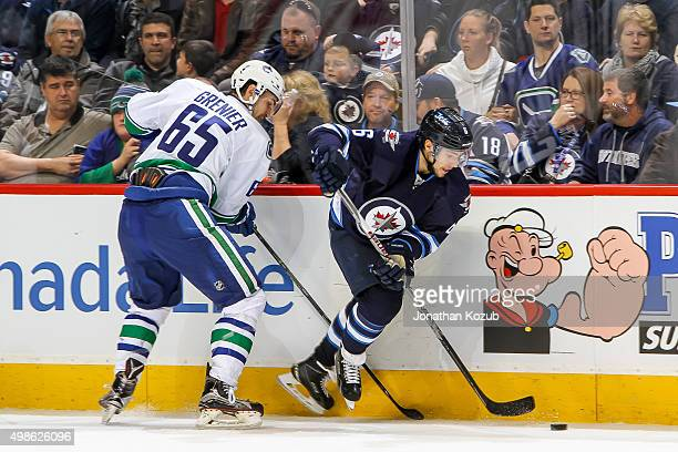 Alexander Burmistrov of the Winnipeg Jets plays the puck along the boards as Alexandre Grenier of the Vancouver Canucks gives chase during third...