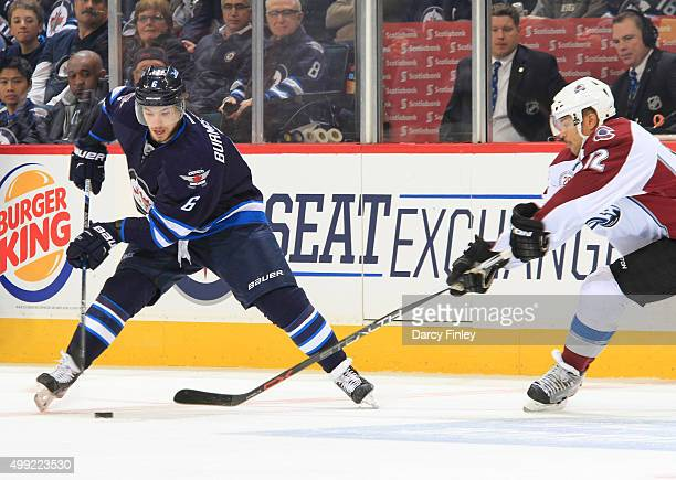 Alexander Burmistrov of the Winnipeg Jets plays the puck as Jarome Iginla of the Colorado Avalanche defends during thirdperiod action at the MTS...