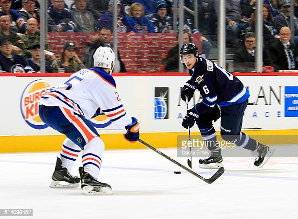 Alexander Burmistrov of the Winnipeg Jets plays the puck up the ice as Darnell Nurse of the Edmonton Oilers defends during second period action at...