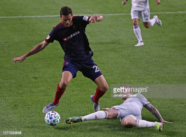 Alexander Buttner of New England Revolution knocks the ball away from Elliot Collier of Chicago Fire at Soldier Field on September 06, 2020 in...