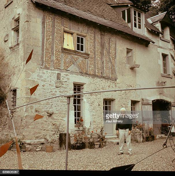 Alexander Calder standing in front of his house in Sache France A sculpture by Calder can be seen in the foreground Ca 19501976
