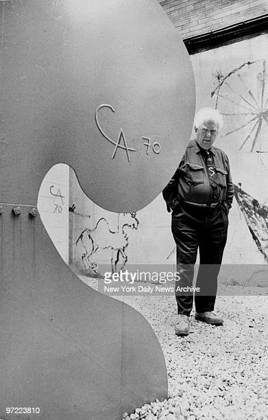 Alexander Calder standing next to one of his renown stabiles sculptures