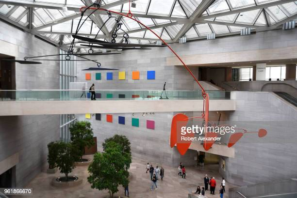 Alexander Calder's untitled aluminum and steel mobile hangs from the ceiling above visitors at the National Gallery of Art East Building on the...