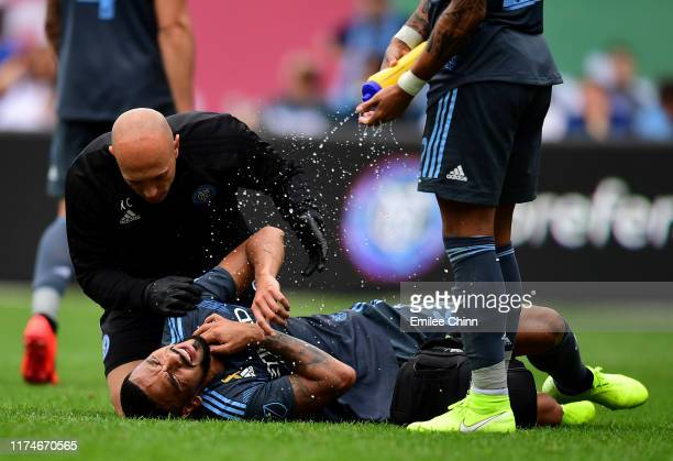 Alexander Callens of New York City FC lays on the ground with a trainer during their game against San Jose at Yankee Stadium on September 14 2019 in...