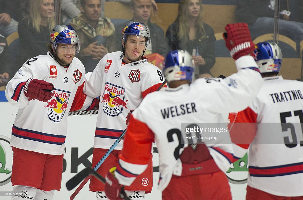 Alexander Cijan #12 of Red Bull Salzburg and team mates Alexander Rauchenwald #9, Daniel Welser #20 and Matthias Trattnig #51 celebrate after Alexander Cijan scored his first goal of the match during the Champions Hockey League group stage game between HV71 Jonkoping and Red Bull Salzburg on August 24, 2014 in Jonkoping, Sweden.