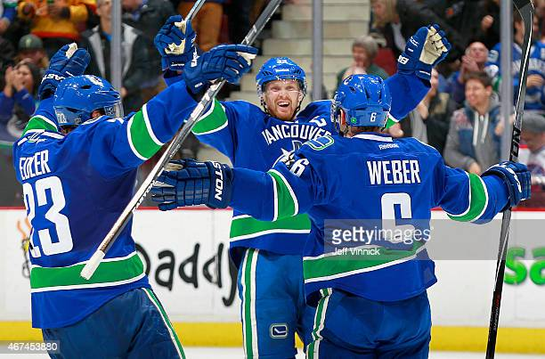 Alexander Edler and Daniel Sedin congratulate Yannick Weber of the Vancouver Canucks who scored against the Winnipeg Jets during their NHL game at...