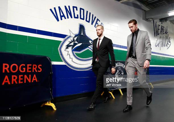 Alexander Edler and Jacob Markstrom of the Vancouver Canucks walk to their dressing room before their NHL game against the Detroit Red Wings at...