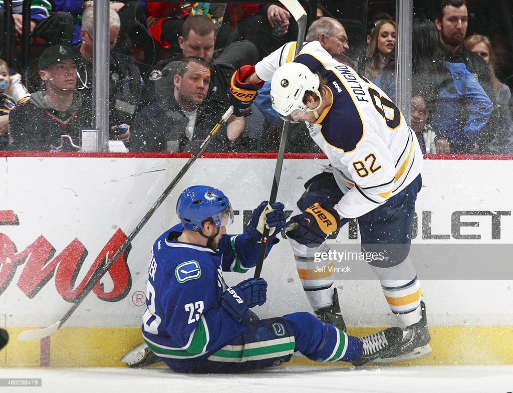 Alexander Edler #23 of the Vancouver Canucks and Marcus Foligno #82 of the Buffalo Sabres collide during their NHL game at Rogers Arena March 23, 2014 in Vancouver, British Columbia, Canada.