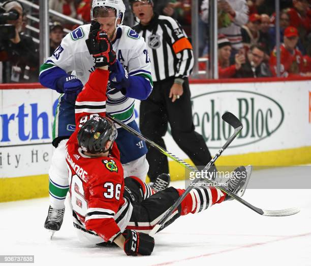 Alexander Edler of the Vancouver Canucks and Matthew Highmore of the Chicago Blackhawks tussle on the ice at the United Center on March 22 2018 in...