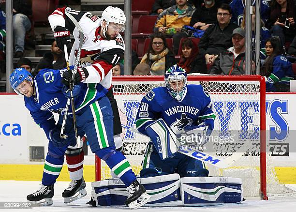 Alexander Edler of the Vancouver Canucks blocks out Martin Hanzal of the Arizona Coyotes as a shot is taken against goaltender Ryan Miller of the...