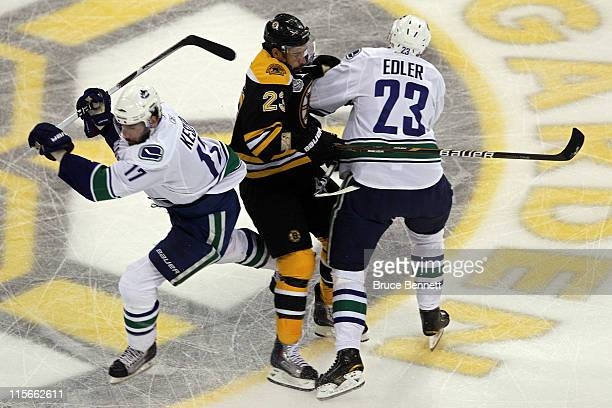 Alexander Edler of the Vancouver Canucks checks Chris Kelly of the Boston Bruins during Game Four of the 2011 NHL Stanley Cup Final at TD Garden on...