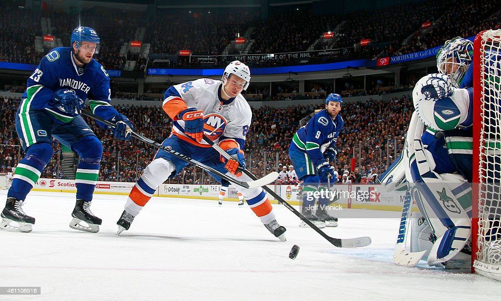 Alexander Edler #23 of the Vancouver Canucks checks Mikhail Grabovski #84 of the New York Islanders in front of Eddie Lack #31 of the Canucks during their NHL game at Rogers Arena January 6, 2015 in Vancouver, British Columbia, Canada. Vancouver won 3-2.