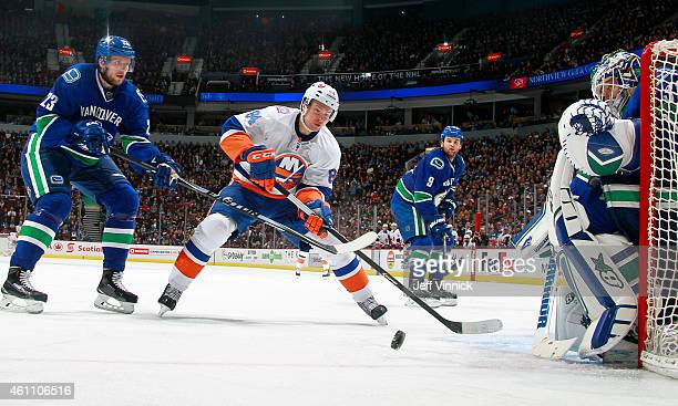 Alexander Edler of the Vancouver Canucks checks Mikhail Grabovski of the New York Islanders in front of Eddie Lack of the Canucks during their NHL...