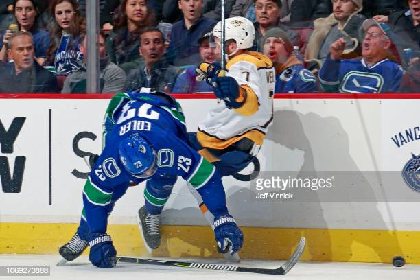 Alexander Edler of the Vancouver Canucks checks Yannick Weber of the Nashville Predators during their NHL game at Rogers Arena December 6, 2018 in...
