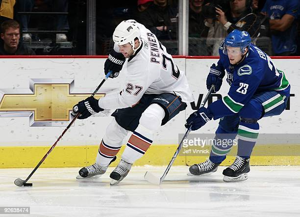 Alexander Edler of the Vancouver Canucks follows close behind as Dustin Penner of the Edmonton Oilers skates up ice with the puck during their game...