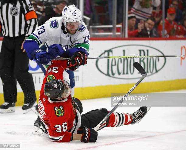 Alexander Edler of the Vancouver Canucks hits Matthew Highmore of the Chicago Blackhawks with his stick at the United Center on March 22 2018 in...