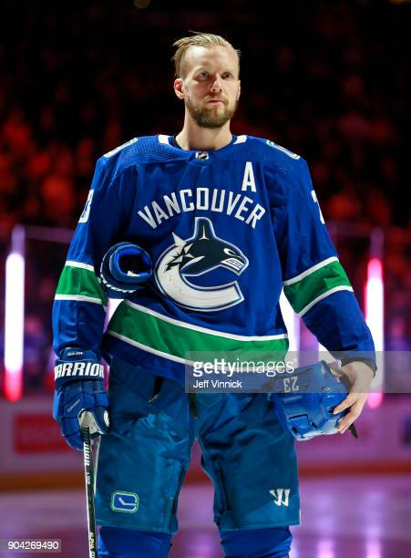 Alexander Edler of the Vancouver Canucks listens to the national anthem during their NHL game against the Calgary Flames at Rogers Arena December 17...