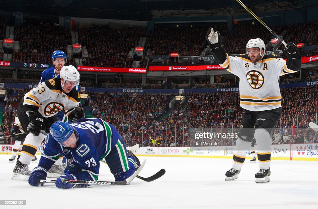 Alexander Edler #23 of the Vancouver Canucks looks on dejected as Patrice Bergeron #37 of the Boston Bruins celebrates the goal of Brad Marchand #63 of the Boston Bruins during their NHL game at Rogers Arena March 13, 2017 in Vancouver, British Columbia, Canada. Boston won 6-3.