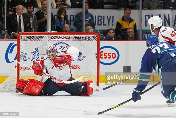 Alexander Edler of the Vancouver Canucks scores his second goal against Michal Neuvirth of the Washington Capitals while Joel Ward of the Capitals...