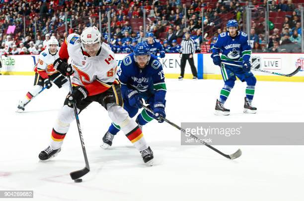 Alexander Edler of the Vancouver Canucks skates after Jaromir Jagr of the Calgary Flames as he skates up ice with the puck during their NHL game at...