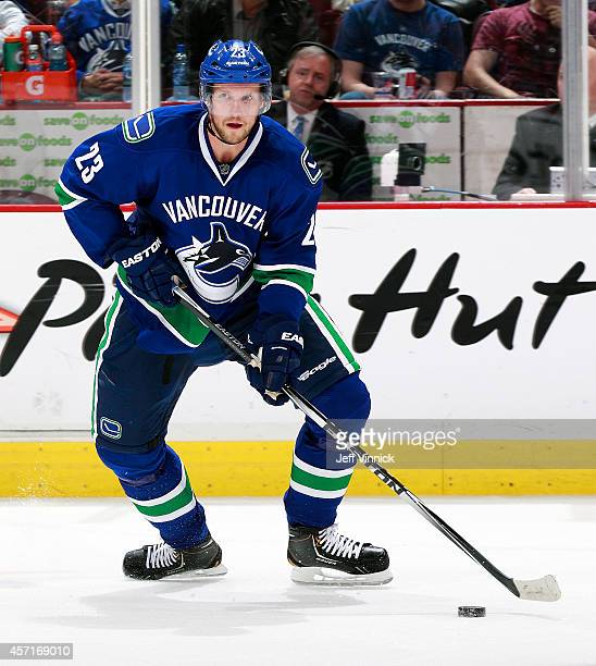 Alexander Edler of the Vancouver Canucks skates up ice with the puck during their NHL game against the Edmonton Oilers at Rogers Arena October 11...