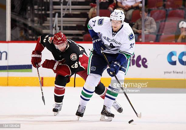 Alexander Edler of the Vancouver Canucks skates with the puck past Cal O'Reilly of the Phoenix Coyotes during the NHL game at Jobingcom Arena on...