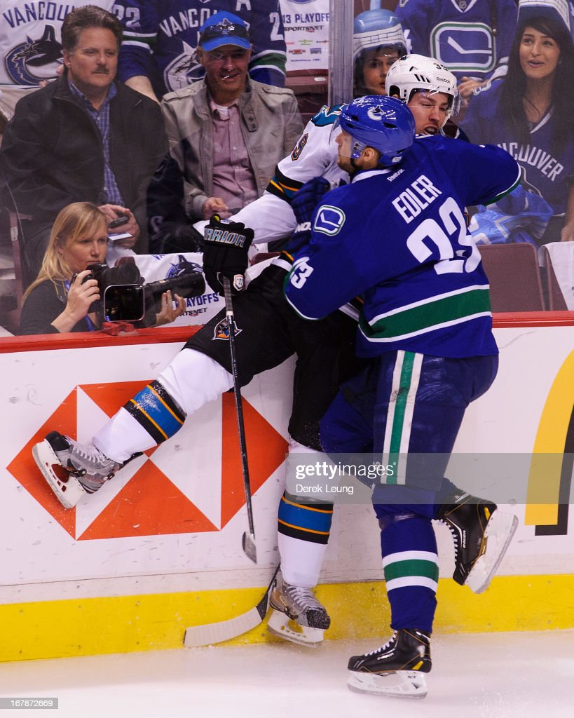 Alexander Edler #23 of the Vancouver Canucks slams Logan Couture #39 of the San Jose Sharks against the boards in Game One of the Western Conference Quarterfinals during the 2013 NHL Stanley Cup Playoffs at Rogers Arena on May 1, 2013 in Vancouver, British Columbia, Canada. The San Jose Sharks won 3-1.