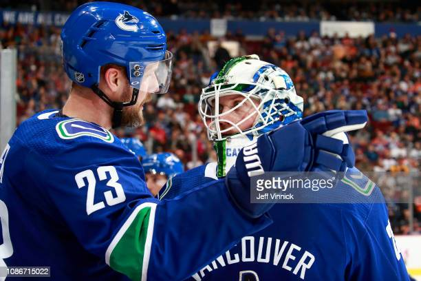 Alexander Edler of the Vancouver Canucks talks to teammate Jacob Markstrom during their NHL game against the Edmonton Oilers at Rogers Arena December...